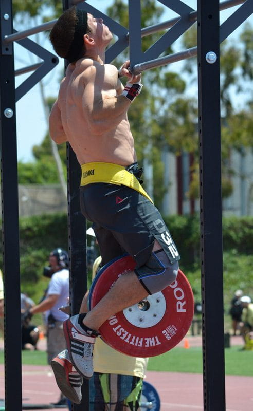 Dan bailey doing Chest to Bar Pull Ups with a weight