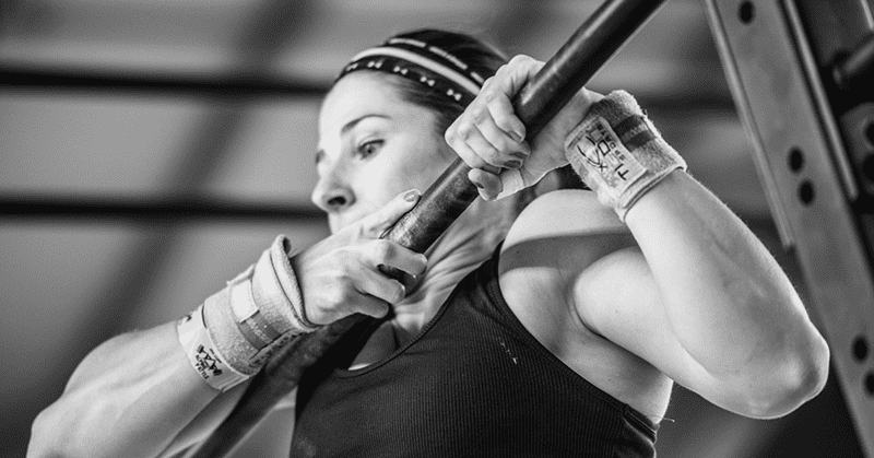 crossfit girl completes bar muscle up exercise
