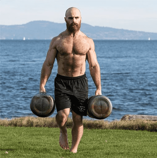 Lucas Parker Crossfit athlete farmer's carries weights outside by the sea whilst doing crossfit grunt work