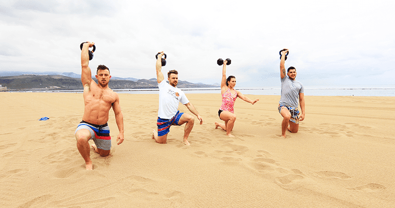 four crossfit athletes on beach dumbell holiday wods