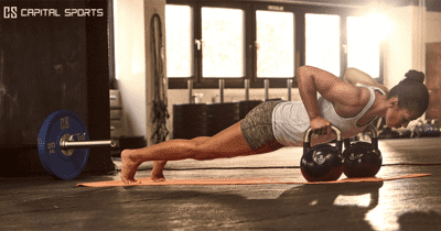 crossfit girl push ups on kettlebells in summer