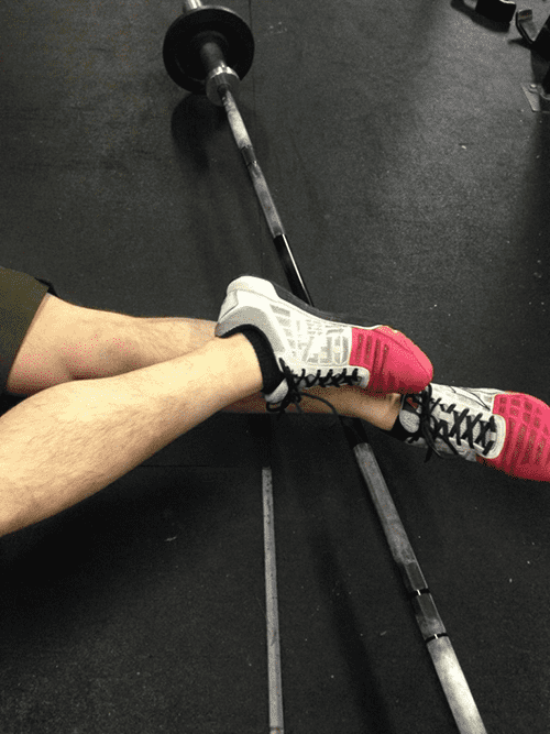 crossfit guy works on ankle mobility by rolling with a barbell