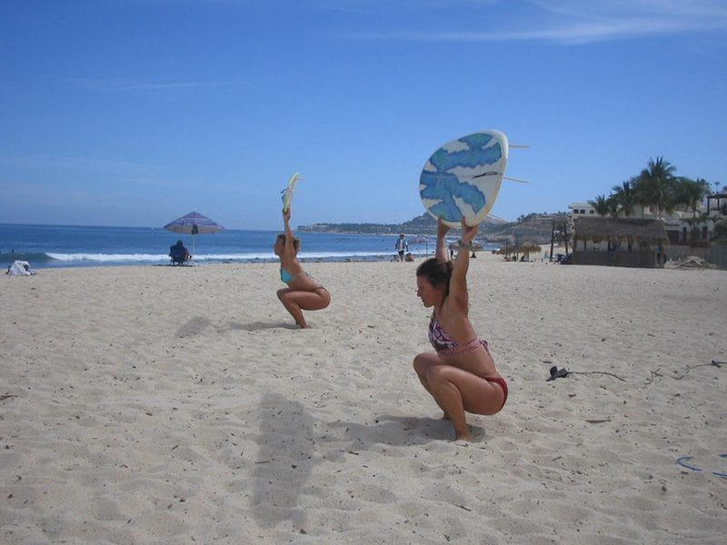 two surfer girls overhead squats holiday wods
