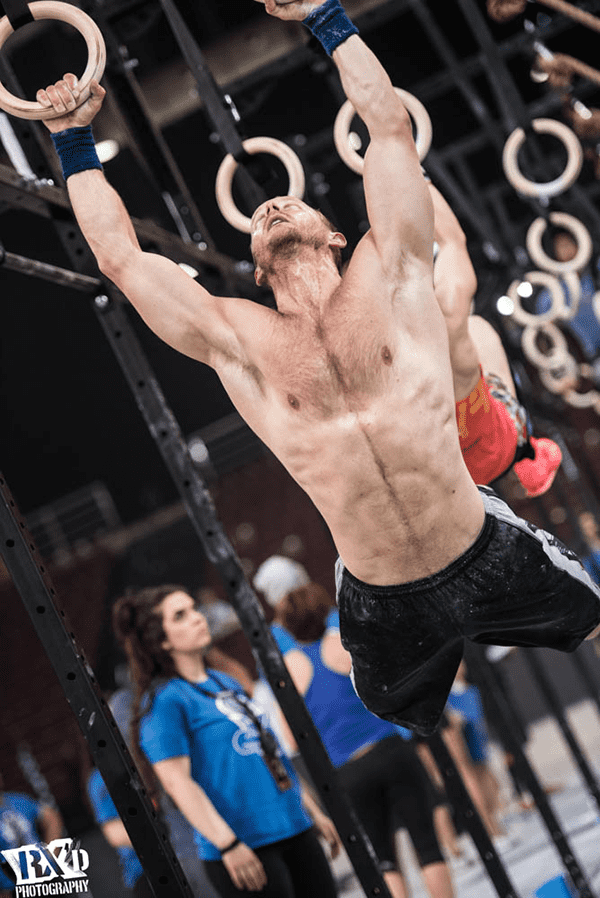 male crossfitter perfroms ring muscle up technique