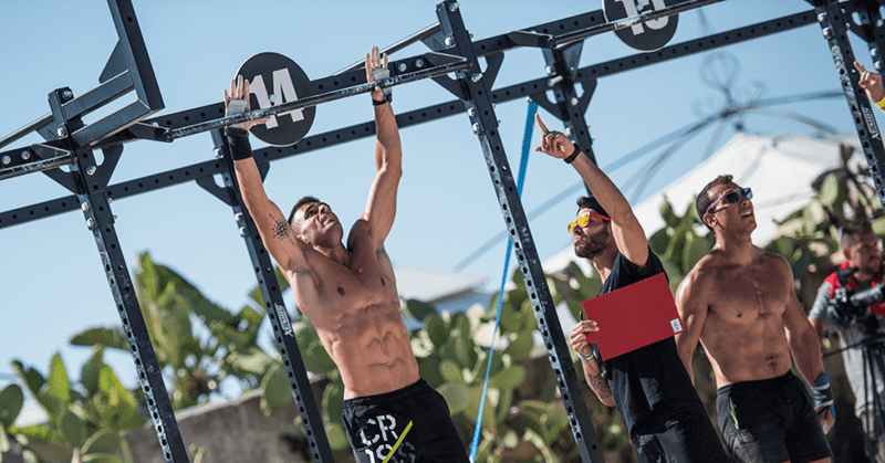 male crossfitters doing pull ups outdoors