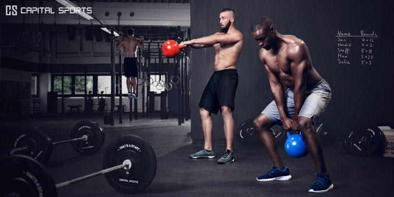 2 male crossfit athletes kettlebell swings to build core strength