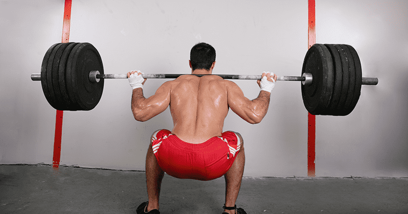 male crossfit athlete squatting 1rm