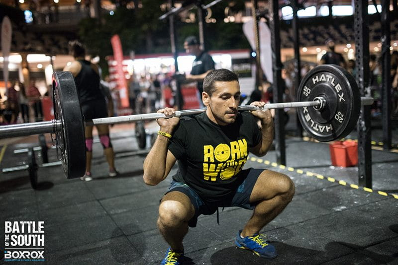 male crossfitter squatting barbell