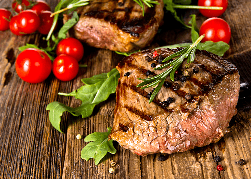 paleo bbq beef steak with tomatoes on wooden board