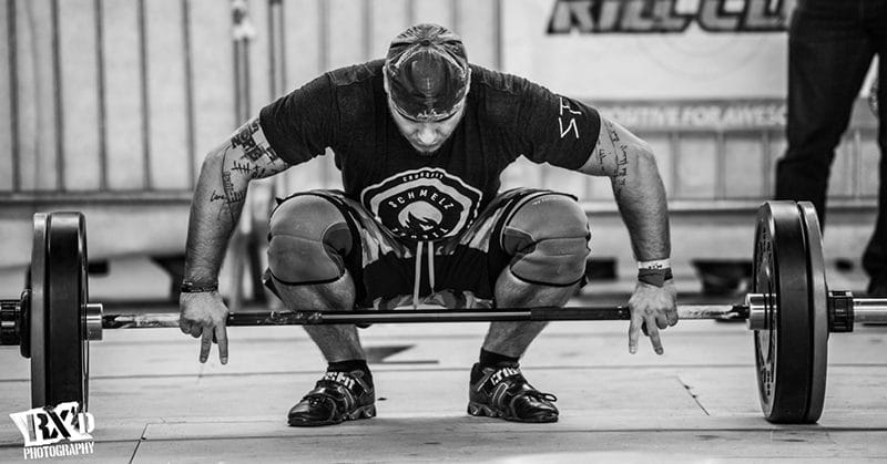 male crossfit athlete snatches barbell during intense crossfit conditioning