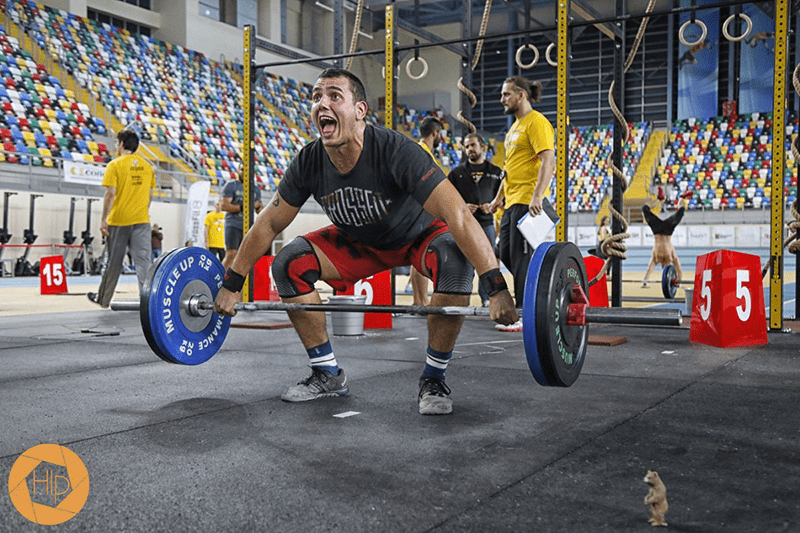 male crossfit athlete snatch with barbell