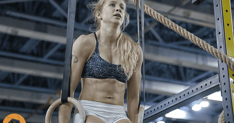 crossfit female performs ring muscle up