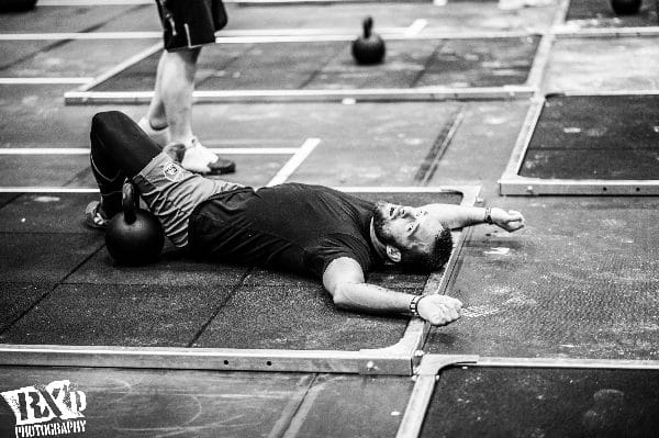 muscle fatigue crossfit athlete lying on floor after WOD