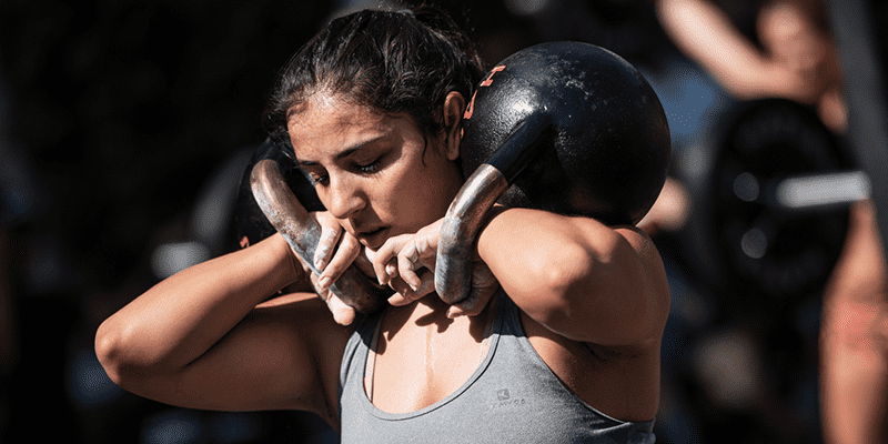 female athlete crossfit training kettlebells