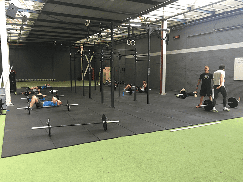 exhausted athletes lie on floor after workout at mobilis crossfit