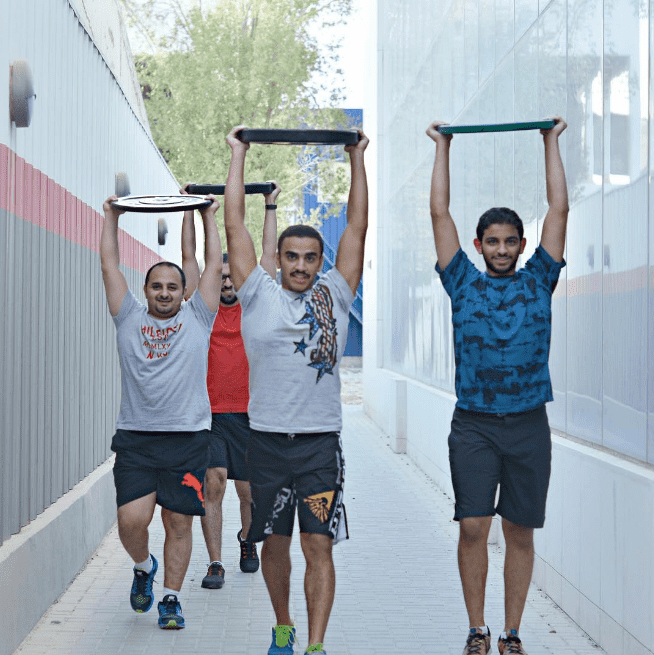 male kuwaiti Crossfitters carrying plates
