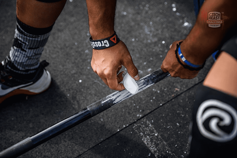 crossfit athlete chalking barbell