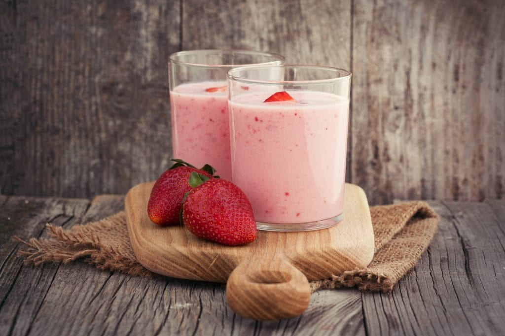Fresh healthy strawberry smoothie on old wooden background