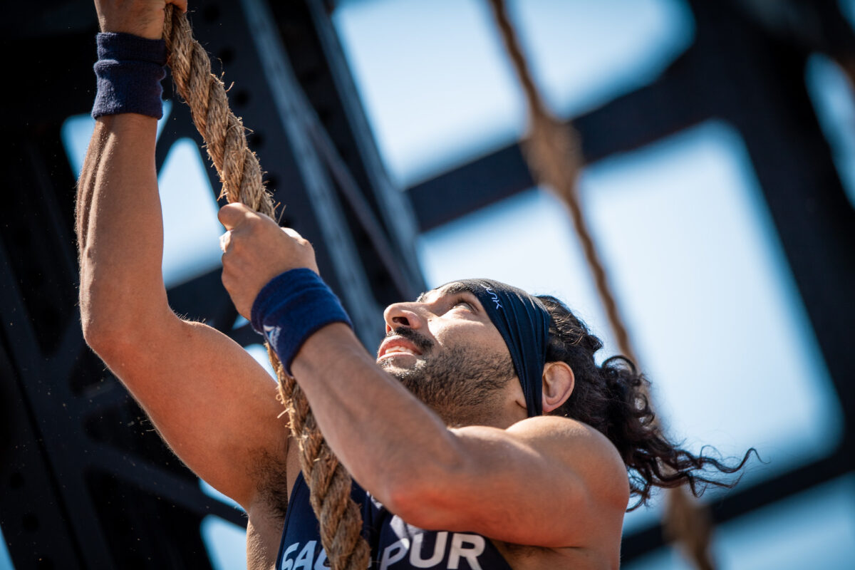 athlete performs rope climb workouts outdoors