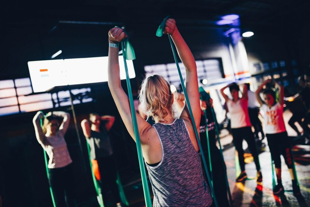 woman performs resistance bands workouts to add variety to training