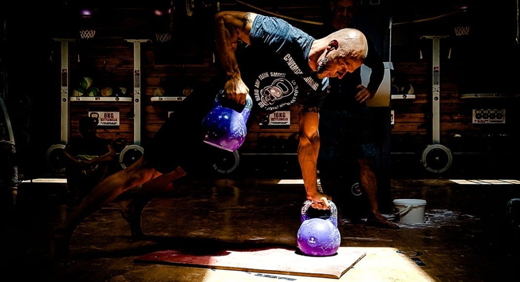 man performs hard kettlebell workout with gorilla cleans