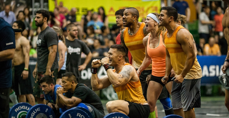 team of athletes cheers during CrossFit event