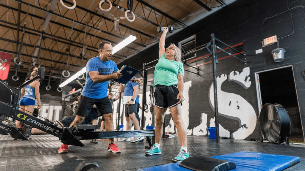 master athlete holds dumbbell overhead at training facility