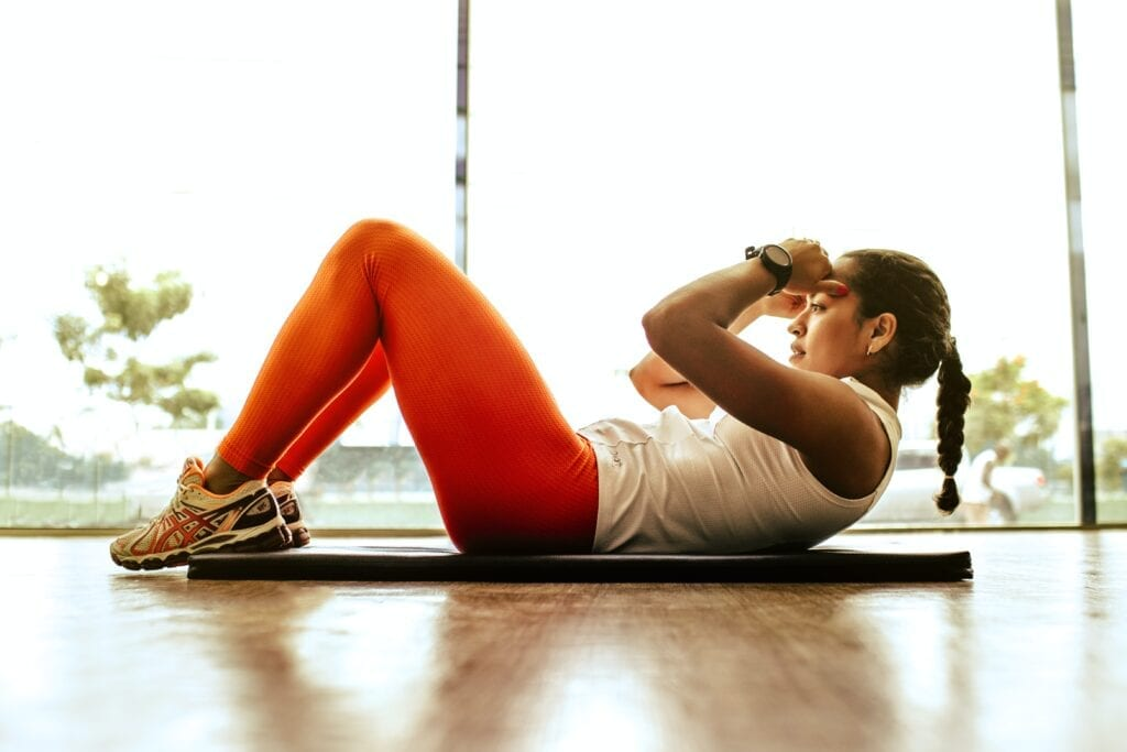 female athlete performs sit up at home