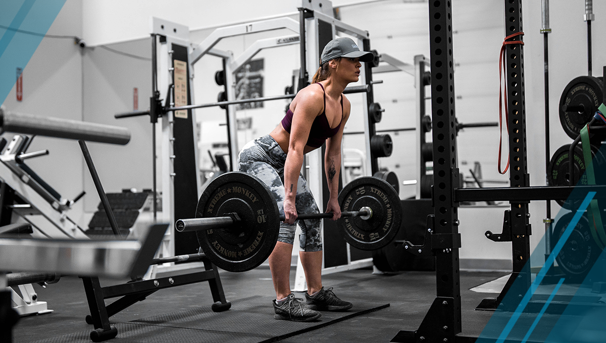 woman performs deadlift workout in gym