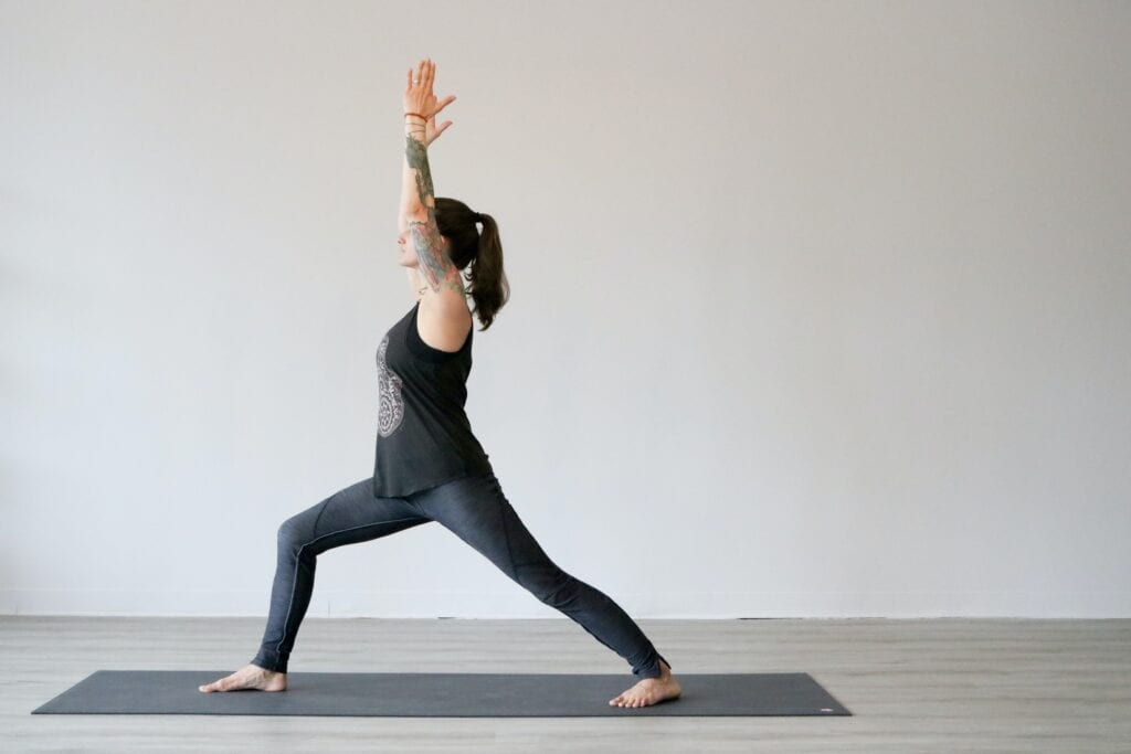 woman performs standing yoga poses and holds warrior 1 pose