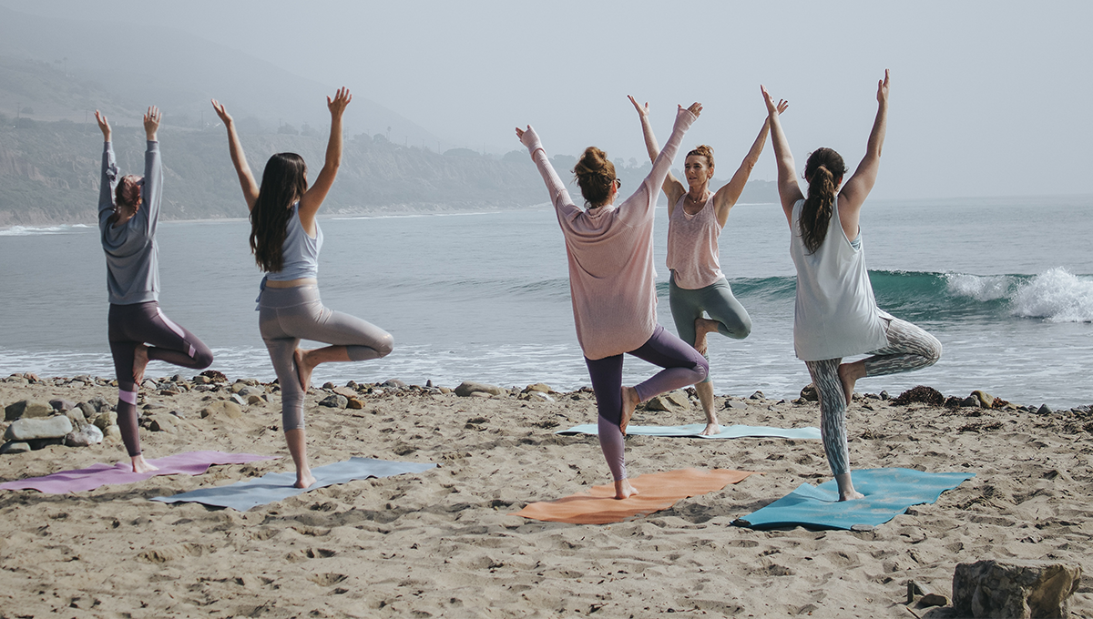 group of women performs standing yoga poses by the beach