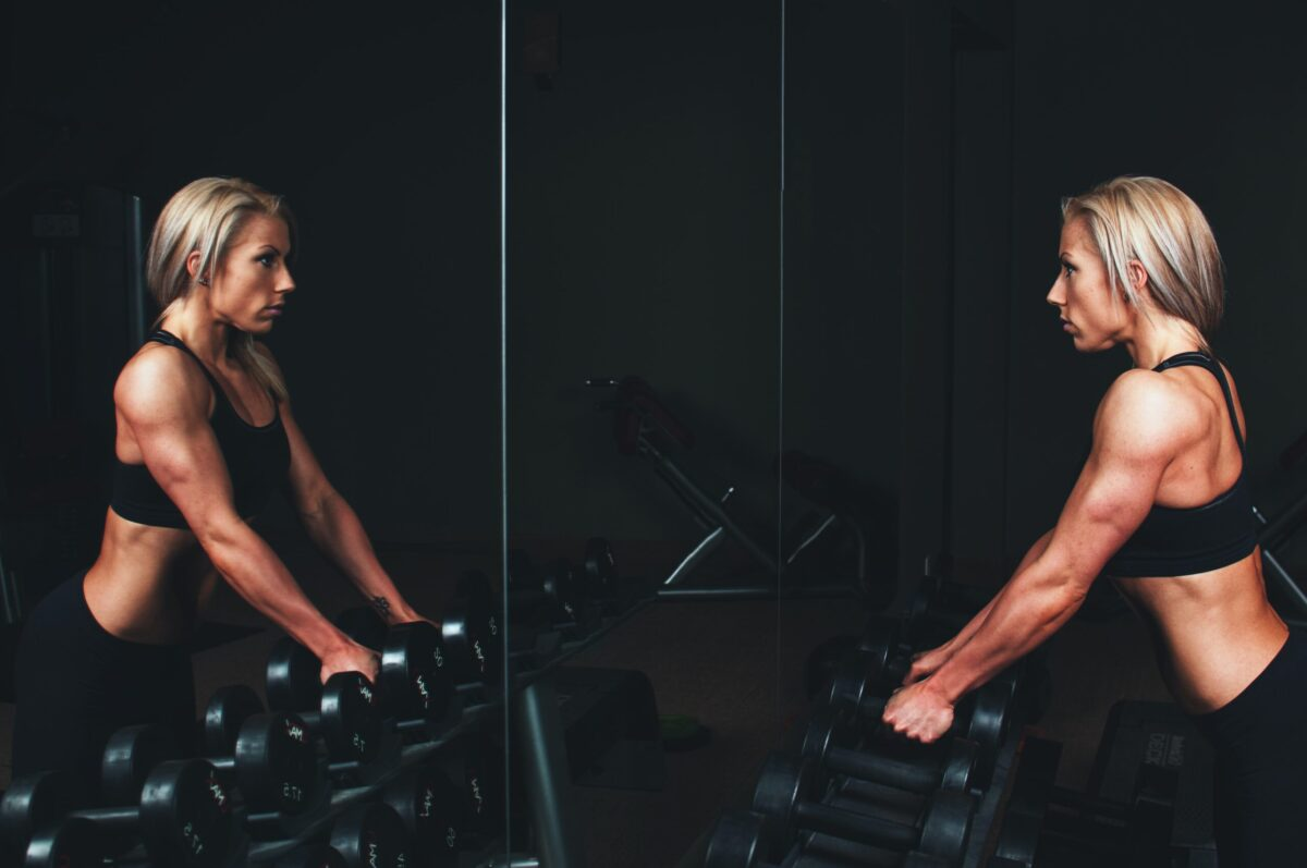 woman readies to perform dumbbell shrugs